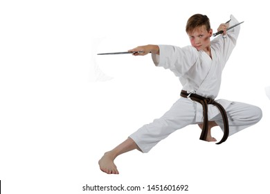 Teenage caucasian boy wearing a karate uniform performing kata with Sai