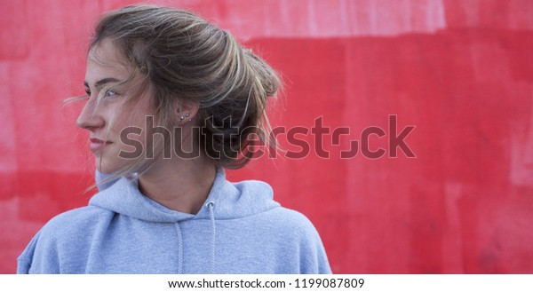 Teenage caucasian girl with brown hair looking at the edge of frame with red painted background.
