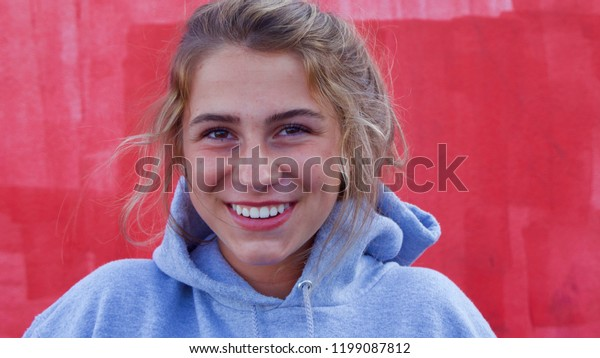 Teenage caucasian girl with brown hair looking at camera smiling.