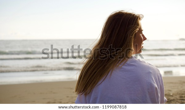 Teenage caucasian girl with brown hair looking at the Pacific Ocean from behind.