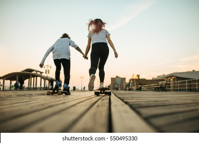 Teenage couple ride longboards on the street from the back