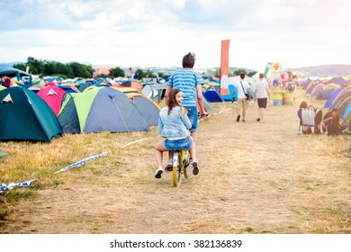 Teenage couple riding bike together at summer music festival