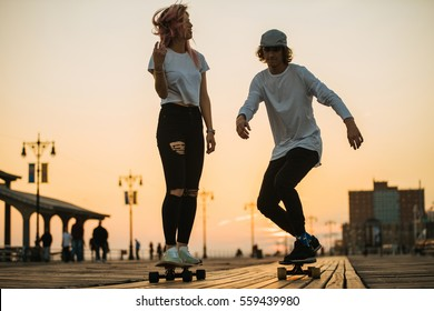 Teenage couple riding longboards on the boardwalk