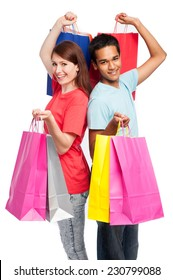 Teenage couple with shopping bags. Studio shot on white background.