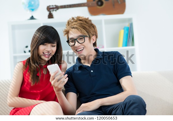 Teenage couple watching something on mobile phone at home
