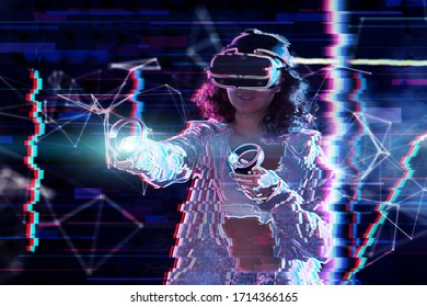 Teenage curly girl is playing in virtual reality game club. Smiling young woman in VR glasses is gaming, using wireless controllers. Entertainment and leisure concept. Modern technologies.