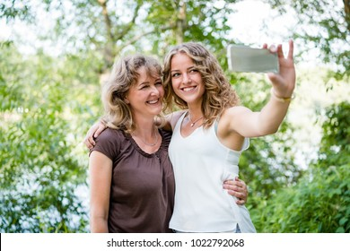 Teenage daughter and her senior mother taking a selfie.