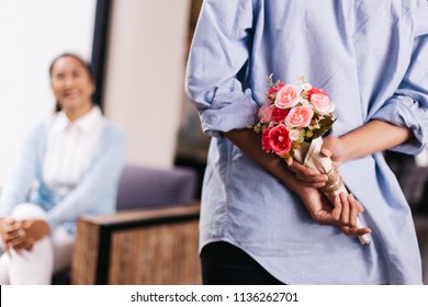 Teenage daughter hiding a surprise bouquet of roses and giving to senior mother on her special day such as mother's day or birthday. Celebration and holiday concept