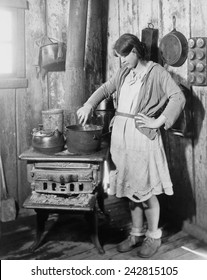 The teenage daughter of a an impoverished Arkansas farmer cooking on an old stove while her mother was in a tuberculosis sanitarium during the Great Depression. Red Cross photo from ca. 1930.