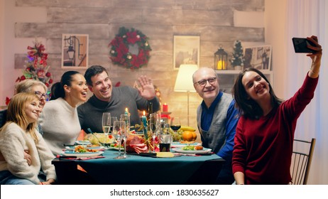 Teenage daughter taking a selfie with the family at christmas reunion. Traditional festive christmas dinner in multigenerational family. Enjoying xmas meal feast in decorated room. Big family reunion