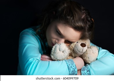 Teenage depression, crying girl holding a teddy bear