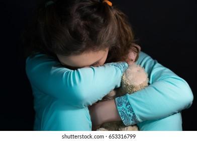 Teenage depression, crying girl holding a teddy bear in the dark