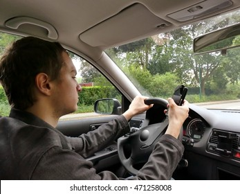 Teenage driver on his cellphone while driving his car. Typing on the smartphone. Dangerous driving concept.