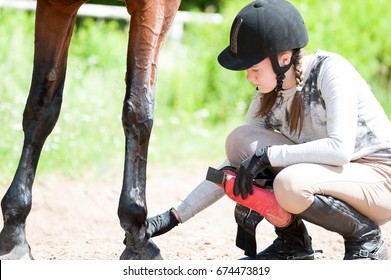 Teenage equestrian girl in helmet sitting near her bay horse and checking for leg injury after sport training. Outdoors horizontal colored image.
