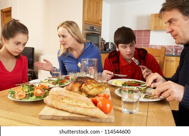 Teenage Family Having Argument Whilst Eating Lunch Together In Kitchen