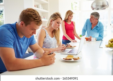Teenage Family Having Breakfast In Kitchen With Laptop