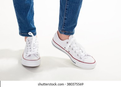 Teenage fashion style on white background. Trendy white gumshoes and jeans on women's legs.