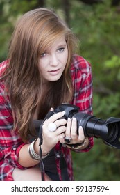 Teenage fasion model holding a camera looking forward