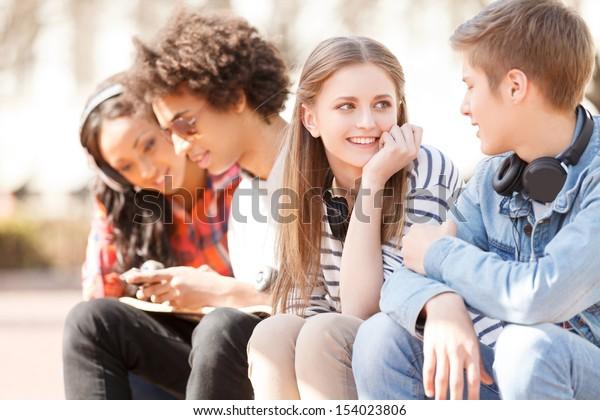 Jugendfreunde. Vier fröhliche Jugendfreunde sprechen miteinander