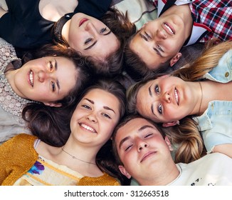 Teenage friends lying together in circle