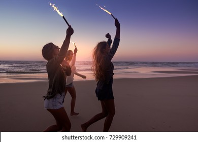 Teenage friends running on a beach with fireworks