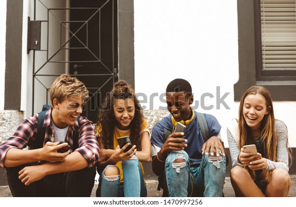 Teenage friends sitting on a pavement holding their mobile phones. Cheerful college boys and girls having fun talking sitting outdoors in a street.