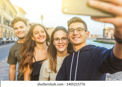 Teenage friends taking a selfie together in the city after school - Lifestyle and friendship concepts with a group of young boys and girls having fun and enjoying time together.