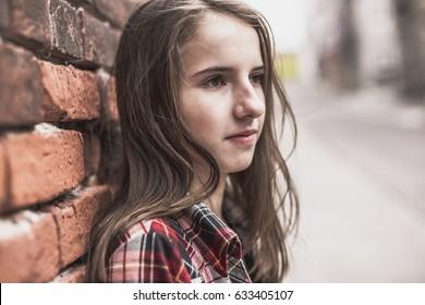 A Teenage girl against a brick wall outside