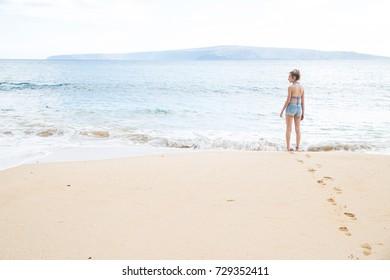 Teenage girl alone at tropical island ocean