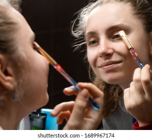 Teenage girl applying make up at home