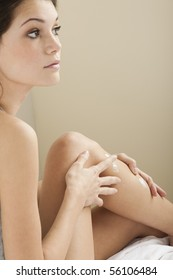 Teenage girl applying moisturizer