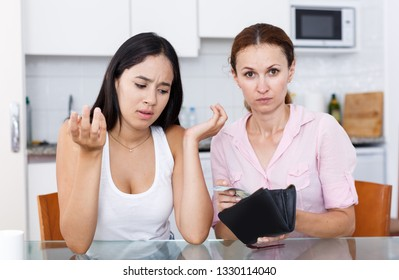 Teenage girl asks her mother some cash in kitchen