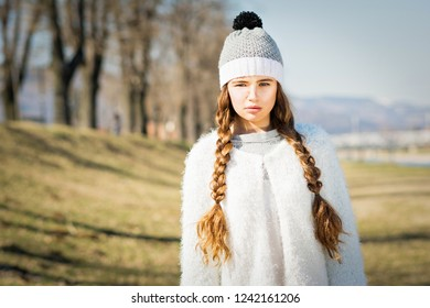 Teenage girl in autumn outdoors in park, with long braided blonde hair. Natural lighting, medium retouch.