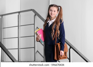Teenage girl with bag and books standing on stairs