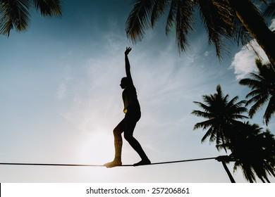 teenage girl  balancing on slackline with sky view on the beach silhouette