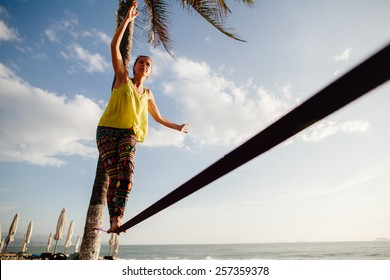 teenage girl  balancing on slackline with sky view on the beach