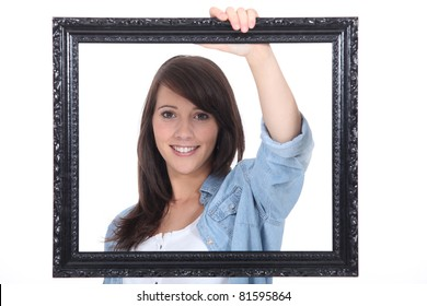 teenage girl behind a painting frame