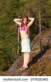 teenage girl in bikini on a rock in a summer forest