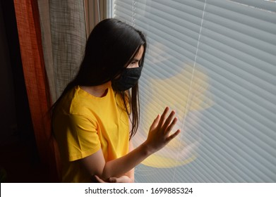 Teenage girl with black flu mask leaning on a window. Her reflection is visible on the glass. She has to stay at home because of the coronavirus pandemic and feels lonely or sad.