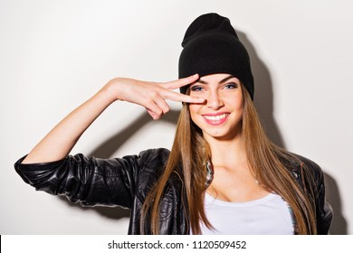 Teenage girl in black leather jacket and beanie hat posing a smiling
