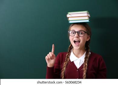 Teenage girl with books on her head standing near green school blackboard