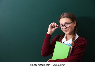 Teenage girl with books standing near green school blackboard