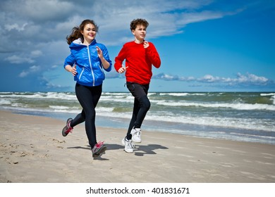 Teenage girl and boy running, jumping on beach
