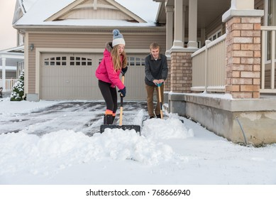 A teenage girl and boy shoveling a snow covered suburban house driveway during winter.