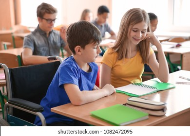 Teenage girl with boy in wheelchair studying at desk in classroom