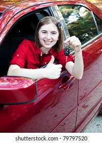 Teenage girl in the car driver's seat, holding keys and giving a thumbs up sign.