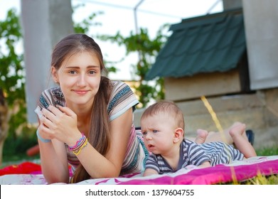 A teenage girl cares for a little boy as a nanny. A nanny and little boy rest together in the garden in the summer and smile