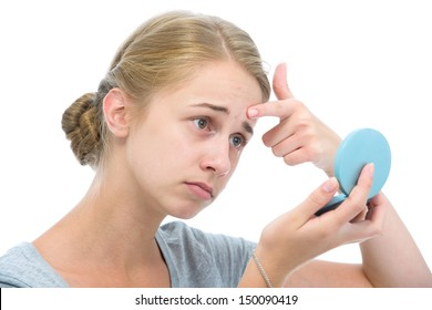 Teenage girl checking her face for pimple in the mirror