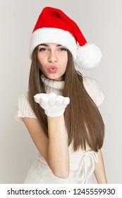 Teenage girl in Christmas hat blowing kisses. Studio lighting, no retouch, closeup.