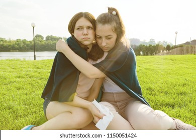 Teenage girl comforts her crying, upset, sad girlfriend. The girls are sitting on the green grass in the park